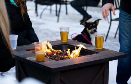 Patrons enjoy Luce Line beers around a fire on the brewery's patio • Photo by Jordan Wipf